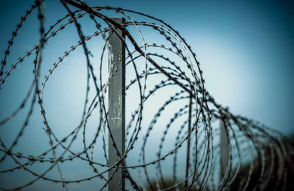 Barbed wire spiral wound on a metal fence against a dark background